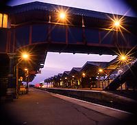 Train heading towards platform on an empty train station at dusk..England, Uk