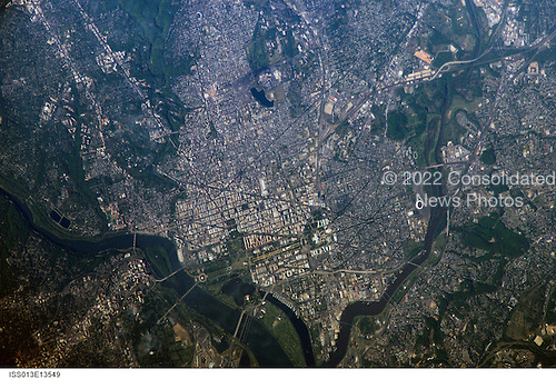 Washington, DC is featured in this image photographed by an Expedition 13 crewmember on the International Space Station on May 2, 2006. George Washington not only served as the namesake for the capital city of the United States, he also chose its location, perhaps envisioning the transportation possibilities that the Potomac River flowing past the site would provide. Early on, the city saw conflict; in the War of 1812, British forces invaded and burned several public buildings. The Civil War marked the beginning of the city's transformation from a provincial town to a world center of culture, history, and political energy during the 20th century. According to the Census Bureau, the District of Columbia, which comprises the city of Washington, supported a population of more than half a million inhabitants in 2003.  This picture was taken as the International Space Station passed over the western border of Maryland and West Virginia. The resolution and extent of the true-color, handheld image is similar to the 15-meter-per-pixel data obtained by sensors onboard the unmanned Landsat-7 and Terra satellites. This resolution is sufficient to capture the sun reflecting off the Capitol Building's dome. Other major landmarks that are visible include the Washington Monument, the Pentagon (bottom left, southwest of the Potomac River), and the Lincoln Memorial, along the northwest bank of the Potomac..Credit: NASA via CNP
