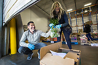 Chris Thompson, owner of Kimball and Thompson Produce, and wife Michelle Thompson help fill orders Saturday, March 21, 2020, at the business in Lowell. They supply fresh produce to the food service industry, including public schools, restaurants and hotels. With many of their usual clients closed due to the covid-19 pandemic, Chris Thompson says they are adapting to get their inventory directly to consumers who need it at wholesale prices. Thompson says he is also reaching out to the Northwest Arkansas Food Bank to make sure nothing goes to waste. <br /> <br /> The business began selling to the public Friday morning, and many shelves were already bare Saturday. Thompson says they will be working to keep their inventory updated as they navigate the temporary change to their business model. <br /> <br /> Staff and family members are pitching in to help fill orders curbside while minimizing personal contact and practicing strict sanitizing measures. Customers are asked to place orders ahead of time by calling 479-872-0200 or emailing orders@ktproduce.com. Pickup times are Monday through Saturday from 9 a.m. to 4 p.m., and Sunday from 11 a.m. to 2 p.m. at 305 S. Lincoln St. in Lowell. <br /> <br /> Check out nwaonline.com/200322Daily/ for today's photo gallery.<br /> (NWA Democrat-Gazette/Ben Goff)