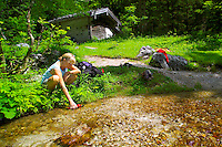Berchtesgaden National Park, Bavavia, Germany, July 2004.  Jillian fills her waterbottle in a creek on the way from St Bartholomy to the Karlinger hut. We are trekking  from hut to hut in the Bavarian mountains of Berchtesgaden. Photo by Frits Meyst/Adventure4ever.com