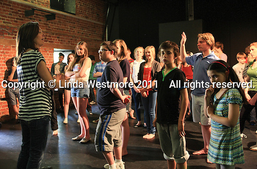 """Assistant Director, Jules Black, talking to the cast.  The Yvonne Arnaud Youth Theatre rehearsing """"The Lion, the Witch and the Wardrobe"""", Guildford, Surrey."""