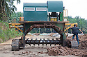 This machine is used to aerate the compost piles by turning them over. Empty fruit bunches (EFBs) left over from the palm oil mill process are recycled at a large on-site composting facility. The rich compost is then used to enrich the soil on the surrounding palm oil plantation. Owned by Kulim, the Sindora Palm Oil Mill and Plantation are green certified by the Roundtable on Sustainable Palm Oil (RSPO) for their environmental, economic, and socially sustainable practices. Johor Bahru, Malaysia