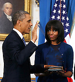 United States President Barack Obama takes the oath of office in front of a portrait of President James Madison as first lady Michelle Obama holds the bible in the Blue Room of the White House in Washington, January 20, 2013. .Credit: Larry Downing / Pool via CNP
