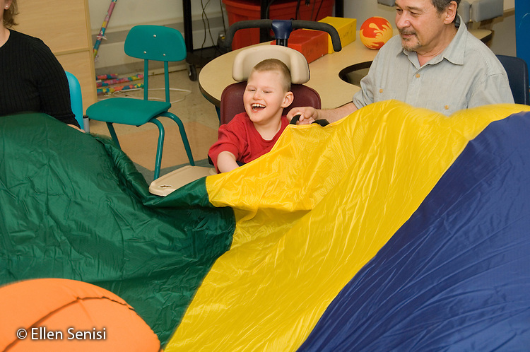 MR / Albany, NY.Langan School at Center for Disability Services .Ungraded private school which serves individuals with multiple disabilities.Child  holds parachute with teaching assistant during lesson with the objective of helping develop coordination and grasping skills while playing. Boy: 9, cerebral palsy, non verbal with expressive and receptive language delays.MR: Law4; Sai2.© Ellen B. Senisi