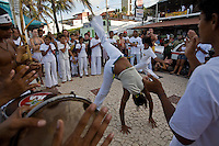 Capoeira, a Brazilian martial art that combines elements of dance, acrobatics and music, and is usually referred to as a game - known for quick and complex moves, using mainly power, speed, and leverage for a wide variety of kicks, spins, and highly mobile techniques - The Roda de capoeira is a circle formed by capoeiristas and capoeira musical instruments, where every participant sings the typical songs and claps their hands following the music - two capoeiristas enter the roda and play the game according to the style required by the musical instruments rhythm. Ponta Negra beach, Natal city, Rio Grande do Norte State, Brazil.