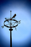 Weather vane against dusky sky vignette