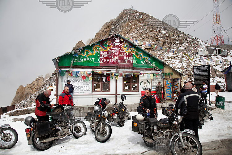 Tourists from Germany and Austria riding Royal Enfield motorcycles stop at the Khardung La Pass to the Nubra Valley. The pass is the highest motorable road in the world at 18,380 ft. Tourists, traveling in small groups, are increasingly renting the classic British motorcycle for trips like this one. At the highest point in the journey is a small resting area with a shrine, prayer flags, and a cafeteria.