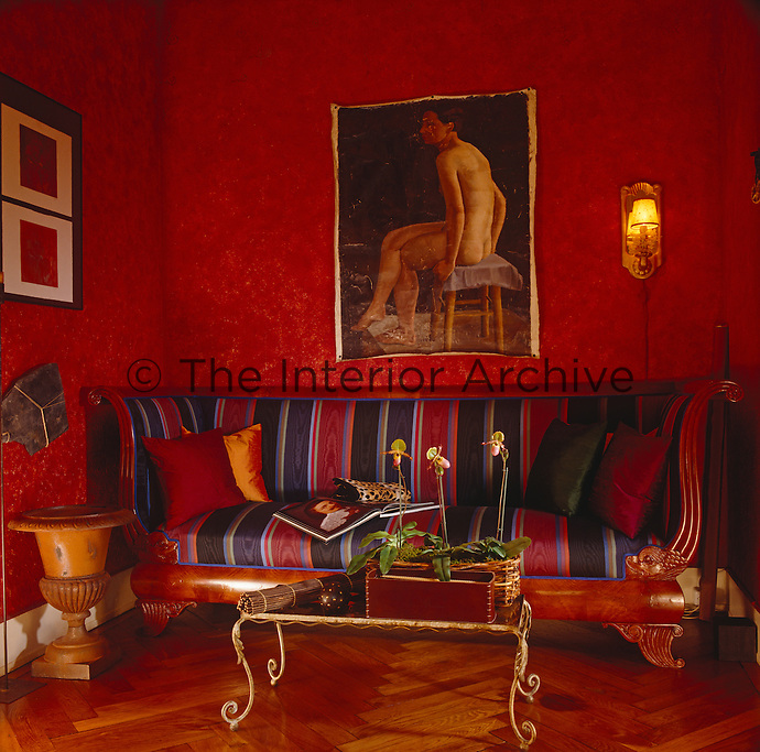 An Empire-style high-backed sofa upholstered in a bold stripe fits snugly across one wall of the small sitting room