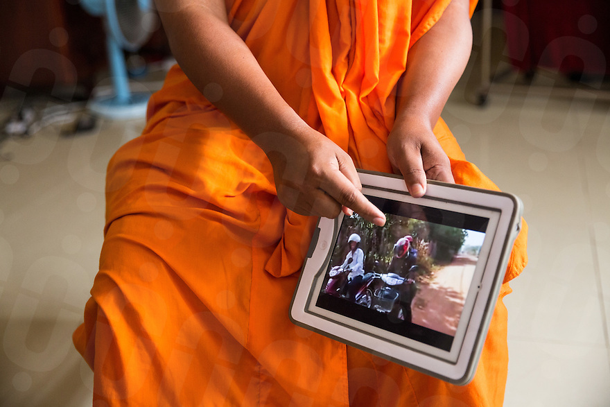 February 02, 2014 - Phnom Penh, Cambodia. Venerable Loun Sovath points out one of his videos on his Ipad. © Nicolas Axelrod / Ruom