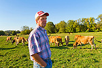 Portrait of Bob Bansen, a dairy farmer in Yamhill, Oregon, standing in the pasture with his herd of Jersey milk cows.
