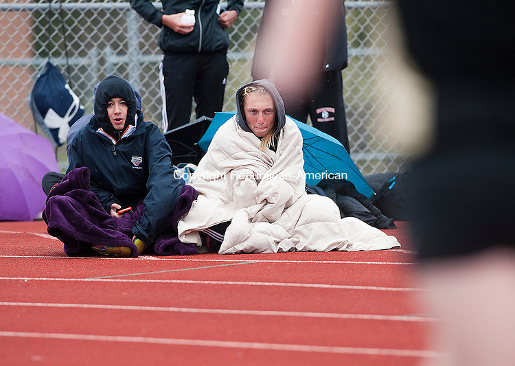 WATERTOWN, CT-0429014JS09-Watching their teammates run, Watertown's Gabby Mayo and Sabrina Viera bundle up from Tuesday's cold temperatures during their track meet against Wolcott and Woodland at Watertown High School.<br /> Jim Shannon Republican-American