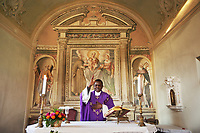 Switzerland. Canton Ticino. Figino. Church «San Francesco». Don Gerald Chukwudi Ani is a catholic priest from Nigeria (Africa). He is celebrating the Vespers' holy mass which is a sunset evening prayer service in the Roman Catholic liturgies of the canonical hours. A painting with The Virgin Mary holding Jesus Christ in her arms with a Franciscan Father on her right. Mary was a 1st-century BC Galilean Jewish woman of Nazareth, and the mother of Jesus, according to the New Testament. The Franciscans are a group of related mendicant religious orders within the Catholic Church, founded in 1209 by Francis of Assisi. These orders include the Order of Friars Minor, the Order of Saint Clare, and the Third Order of Saint Francis. A chalice or goblet is a footed cup intended to hold a drink. In religious practice, a chalice is often used for drinking during a ceremony or may carry a certain symbolic meaning. A paten, or diskos, is a small plate, usually made of silver or gold, used to hold Eucharistic bread which is to be consecrated. It is generally used during the service itself, while the reserved sacrament are stored in the tabernacle in a ciborium. 23.03.2018 © 2018 Didier Ruef