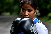 INDIA (West Bengal - Calcutta)July 2010, Sanno Babe (right) during her practice. Shakila and Shanno are twins from a poor muslim family of Iqbalpur, Kolkata. . Inspite of their late father's unwillingness to send his daughters to take up  boxing her mother Banno Begum inspired them to take up boxing at the age of 3. Their father was more concerned about the social stigma they have in their community regarding women coming into sports or doing anything which may show disrespect to the religious emotions of his community. Shakila now has been recognised as one of the best young woman boxers of the country after she won the  international championship at Turkey in the junior category. Shanno is also been called for the National camp this year. Presently Shakila and shanno has become the role model in the Iqbalpur area  and parents from muslim community of Iqbalpur have started showing interst in boxing. Iqbalpur is a poor muslim dominated area mostly covered with shanty town with all odds which comes along with poverty and lack of education. - Arindam Mukherjee