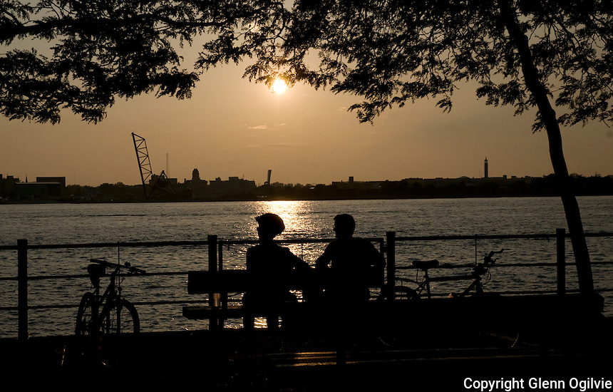Cyclists take a break from riding to enjoy the sunset along the Sarnia Bay waterfront.