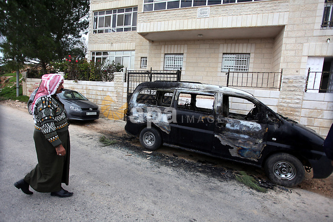 A Palestinian man inspects a burnt vehicle following an apparent price tag attack by Jewish settlers in the West Bank village of Deir Jarir, northeast of Ramallah, on February 5, 2013. Suspected Jewish extremists torched a vehicle and scrawled Hebrew graffiti on a nearby wall in the village, Palestinians and Israelis said. Photo by Issam Rimawi