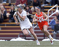 Boston College midfielder Mikaela Rix (17) brings the ball forward as Syracuse University attacker Devon Collins (44) closes.  Syracuse University (orange) defeated Boston College (white), 17-12, on the Newton Campus Lacrosse Field at Boston College, on March 27, 2013.