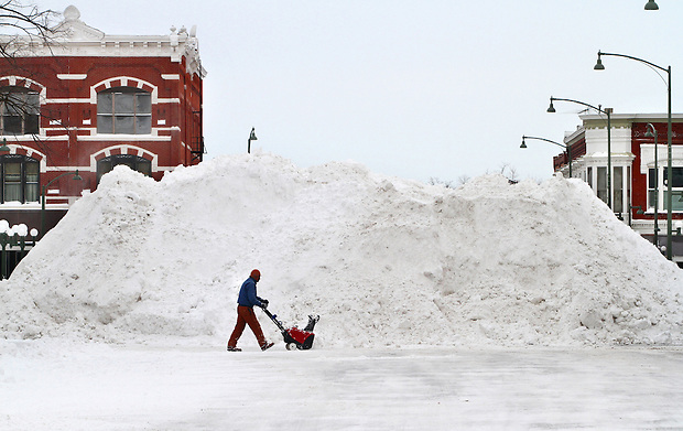 While helping the city dig out from heavy snowfall, Ed Dieleman walks past a 20-foot pile of snow in the town square of Oskaloosa, Iowa on Wednesday, February 2, 2011.  Many Oskaloosa residents are saying the heaps are the largest they've ever seen.
