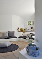 The location of the villa has influenced the design of the living room with a floor of granite tiles and concrete banquettes strewn with comfortable cushions