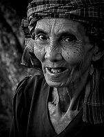 Black and white Portrait of an elderly Khmer women who collects plastic bottles left by tourists at Angkor Wat, Cambodia