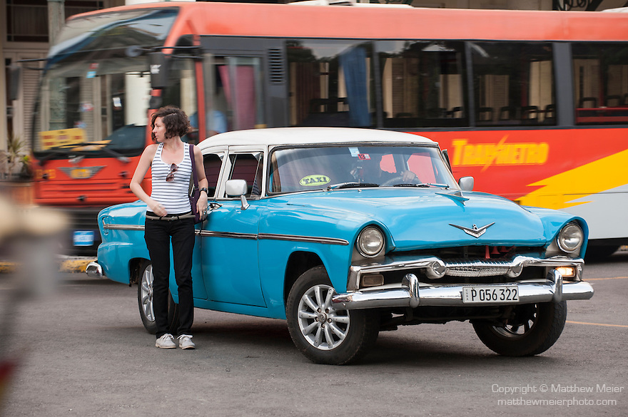 Havana, Cuba; a classic teal blue and white 1955 Plymouth serves as a taxi along the Paseo de Marti