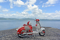 A customised red and white Lambretta scooter (model 'Li' series 2, 150 cc, circa 1962) parked on a lake's shore.