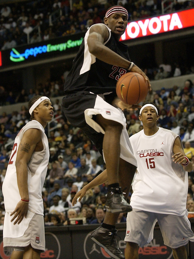 Silver team's Shannon Brown, left, and J.R. Giddens (15) watch Black team's LeBron James (23) fly by during the second half of the Jordan Capital Classic national game won by the silver team 107-102, Thursday, April 17, 2003, in Washington. James had 34 points.(AP Photo/Nick Wass)
