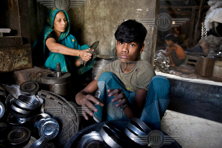 14 year old Jashim works at a factory, which employs many children, producing metal lunch boxes.
