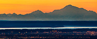 Sunset over the city of Anchorage situated along Cook Inlet with Mt. Denali (right) and Mt. foraker of the Alaska Range mountains in the background.