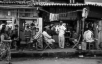woman walks past barber shops on the streets on Mumbai, India.  January, 2000