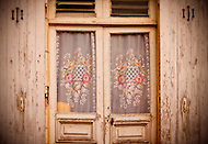Colorful handmade curtains cover the windows of an old weathered wooden door, the entrance to a home in France