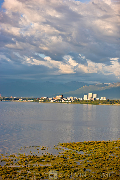 Thunderstorm clouds above the Anchorage, the city skyline reflected in the waters of Knik Arm at high tide, coastal mudflats in the foreground, late afternoon light, Chugach mountains in the background, Anchorage, Southcentral Alaska, Summer.