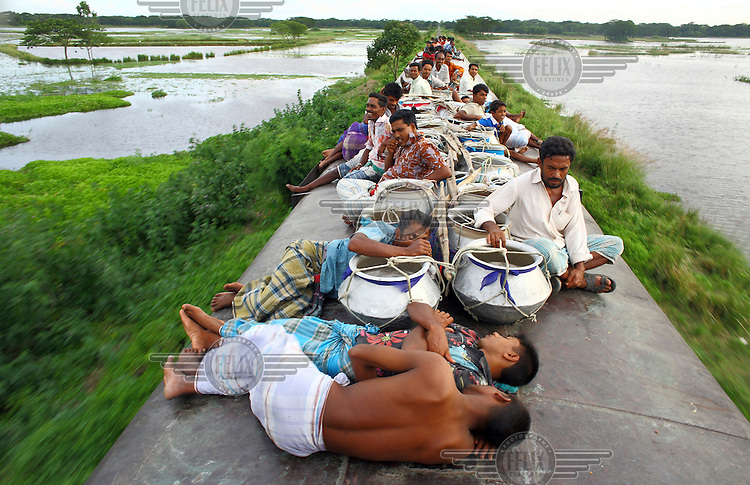 Fishermen, on their journey from market in Dhaka, sleep on the train roof among their empty fish pots. They hope to avoid the 60 taka (£0.55GBP) fare by using the roof and since they can only earn a maximum of 120 taka (£1.10GBP) from their fish the saving is vital. In Bangladesh many people ride on the roofs of trains as frequently that is the only space available. For others, the fares are too high and can be avoided or reduced by travelling on the roof. However, this practice also leads to regular accidents, many of them fatal..