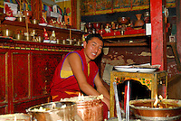 Tibetan Buddhist monk prepares yak butter lamps in a small chapel on the northeast side of the Potala Palace, Lhasa, Tibet, China.