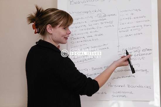 Woman tutor using flip chart during training session for service users,