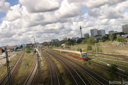 An S-bahn train shoots pass east Berlin under a blanket of clouds. .
