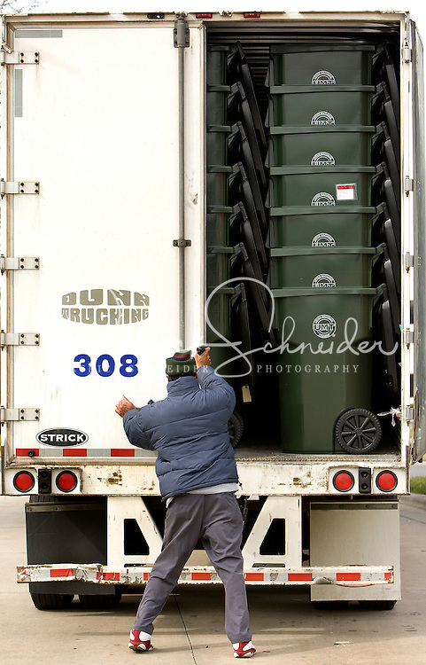 A truck driver prepares to close the back of a truck filled with plastic trash cans as they prepare to be shipped out at SSI Schaefer plastic manufacturing in Charlotte, NC.