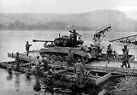 BNPS.co.uk (01202 558833)<br /> NARA/BNPS<br /> <br /> A tank is carried across the Rhine River on March 12 by a pontoon ferry. <br /> <br /> Remarkable rarely seen photos of heroic Allied soldiers fighting their way across Europe before crossing the River Rhine 75 years ago feature in a new book.<br /> <br /> They are published in Images of War, Montgomery's Rhine Crossing, which tells the story of the legendary offensive, nicknamed Operation Plunder, in March 1945.<br /> <br /> On the night of March 23, Field Marshal Bernard Montgomery's 21st Army Group launched a massive artillery, amphibious and airborne assault to breach the historic defensive water barrier protecting northern Germany.<br /> <br /> At the same time, the Americans, with the support of the British 6th Airborne Division, set in motion Operation Varsity - involving 16,000 paratroopers - on the east bank of the Rhine. They were dropped here to seize bridges to prevent German reinforcements from contesting the bridgeheads.<br /> <br /> Fierce fighting ensued, with much bloodshed on both sides as the Allies met determined resistance from machine gun nests. But the daring operation proved successful, helping to considerably shorten the war - the Nazis surrendered just six weeks later.