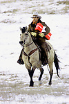 Cowboy on horseback delivering a red Christmas gift box in South Dakota.