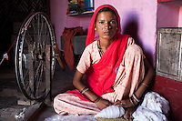 Suki (not her real name), sits for a portrait next to the hand loom in her house in Jhaju village, Bikaner, Rajasthan, India on 4th October 2012. Now 20, Suki was married off at age 12, but only went to live with her husband when she was 14. The three sisters, aged 10, 12, and 15 were married off on the same day by their maternal grandfather while their father was hospitalized. Her husband died three years after she moved in, leaving her with a daughter, now 6, and a son, now 4. She has no parents-in-laws and thus returned to her parents house after being widowed because her brother-in-law, who had become the head of the family after his brother's death, had refused to allow Suki to inherit her deceased husband's fair share of agriculture land. Although Suki's father wants her to remarry, she refuses to, hoping instead to be able to support her family through embroidery and tailoring work. The family also makes hand-loom cotton to subsidize their collective household income. Photo by Suzanne Lee for PLAN UK