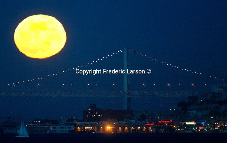 San Francisco Fisherman's Wharf and the Oakland Bay Bridge had a  full moon as a backdrop.