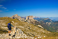 Walker stands on the summit of La Montagnette in the Drome looking towards Mt. Aiguille, Le Grand Veymont, the Sommet de Peyre-Rouge and the escarpment of the High Vercors Plateau with the Valley of the Drac on the right looking towards Grenoble, Isere. France.