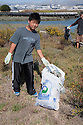 "Peter from Mills High School doing his part to clean up Bayfront Park. Volunteers in the City of Millbrae participated in California Coastal Cleanup Day on 9/19/09. Participants cleaned up inland locations throughout the city as well as at Bayfront Park on the San Francisco Bay shoreline. The inland cleanup efforts were important because, according to the California Coastal Commission, ""past Coastal Cleanup Day data tell us that most (between 60-80 percent) of the debris on our beaches and shorelines comes from inland sources, traveling through storm drains or creeks out to the beaches and ocean. Rain or even something as simple as hosing down a sidewalk can wash cigarette butts, bits of styrofoam, pesticides, and oil into the storm drains and out to the ocean."" The California Coastal Cleanup Day (http://www.coastal.ca.gov/publiced/ccd/ccd.html) is sponsored by the California Coastal Commission and is a part of the International Coastal Cleanup organized by The Ocean Conservancy."