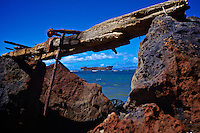 An offshore wrecked oil tanker is framed by rusty and weather-worn shipwreck debris at Kaiolohia Beach (a.k.a. Shipwreck Beach), Lana'i.