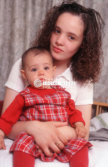 Teenage mother holding baby daughter,