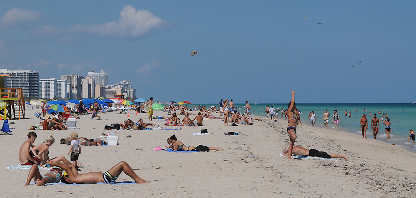 A woman practices yoga, while others enyoy, the sun sand and warm ocean waters of beautiful South Beach, Miami Beach Florida.