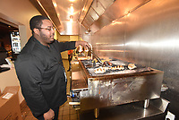 NWA Democrat-Gazette/FLIP PUTTHOFF<br /> Dominique Johnson grills cheeseburgers and chicken on Saturday Feb. 24 2018 at Malco Razorback Cinema in Fayetteville. A grill is a new addition to the kitchen at the theater.