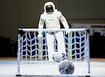 Honda's humanoid robot Asimo kicks a soccer ball during a display at Robo Japan 2008 in Yokohama, Japan.