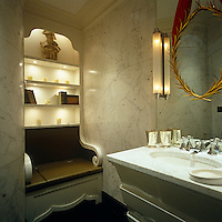 In this small bathroom the walls are covered in marble and the toilet is disguised as a wooden throne