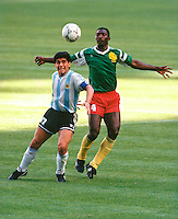 Argentina's World Cup Star Diego Maradona is closely marked by Cameroon's Benjamin Massing during their match at World Cup Italia 90 in Milan's San Siro stadium on June 8th 1990.