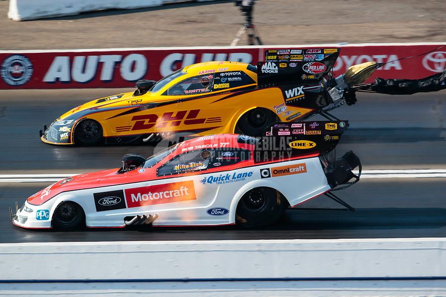 Nov 11, 2018; Pomona, CA, USA; NHRA funny car driver Bob Tasca III (near) races alongside J.R. Todd during the Auto Club Finals at Auto Club Raceway. Mandatory Credit: Mark J. Rebilas-USA TODAY Sports